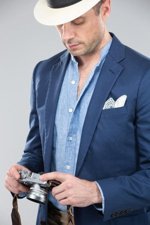 blue-linen-band-collar-shirt-cotton-blazer-khaki-pants-holding-camera-panama-hat